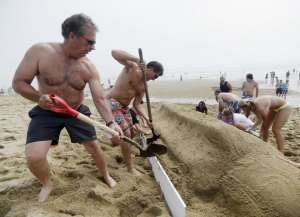 We shall build sand castles with strangers and shovels. (Photo Credit :www.pressherald.com)